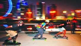 Riders zoom past participants at the 'freestyle session' organised by the Doha Longboarding Crew at