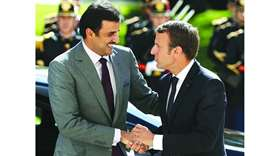 French President Emmanuel Macron (R) greets His Highness Sheikh Tamim bin Hamad al-Thani at the Elys