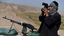 A anti-Taliban armed Afghan fighter keeping watch with binoculars at an outpost during a patrol agai