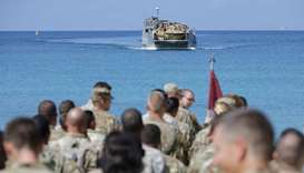 Soldiers from the 602nd Area Support Medical Company wait on a beach for a Navy landing craft