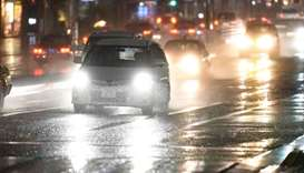 Vehicles drive through rain caused by weather patterns from Typhoon Talim in Tokyo