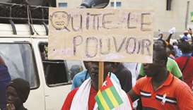 A man holds up a sign which reads 'leave power' during opposition protest in Lome earlier this month