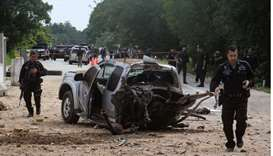 Thai army rangers walk through the scene of a roadside bomb which killed four army rangers in the re