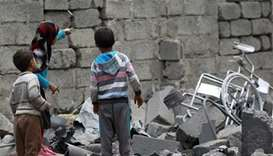 Yemeni children stand amidst the rubble of a house in Sanaa after it was reportedly hit by a Saudi-l