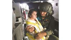 A survivor is held by Turkish military personnel in a helicopter in Kandira after she was rescued fr