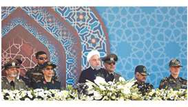 Iranian President Hassan Rouhani sits among senior army staff as he delivers his speech during the a