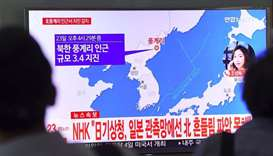 People watch a television news showing a map of the epicenter of an earthquake in North Korea