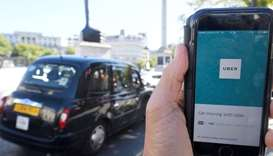 London taxi passing as the Uber app logo is displayed on a mobile telephone