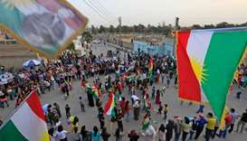 Kurds dance with the Kurdish flag as they celebrate  in support of the independence referendum