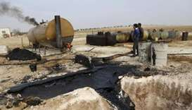 People work at a makeshift oil refinery site in Marchmarin town, Idlib, Syria.