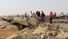 People look at the damage on a bridge hit by a Saudi-led air strike near the northwestern city of Ha
