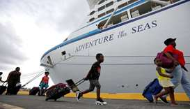 A family carries their luggage to Royal Caribbean's Adventure of the Seas, a mercy ship that took ev