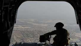 A US soldier sits in the rear of Chinook helicopter while flying over Kabul.