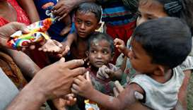 Rohingya refugees stretch their hands for food after crossing the Bangladesh-Myanmar border, in Tekn