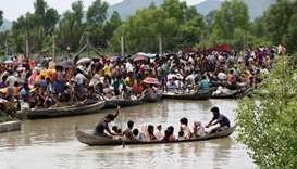 A boat carrying Rohingya refugees is seen leaving Myanmar through Naf river while thousands other wa