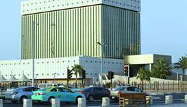 Cars drive past the building of the Qatar Central Bank in Doha.