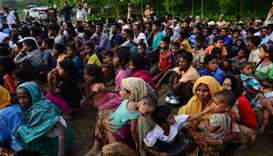Rohingya people wait for relief supplies near a refugee camp