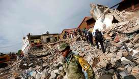 Soldiers work to remove the debris of a house destroyed in an earthquake that struck off the souther