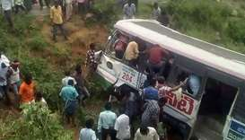 Onlookers and rescuers gather around a bus that crashed in Jagtial district in India's southern Tela