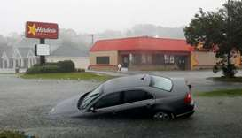 A car washed away by flood waters remains partially submerged as torrential rains continue after Hur