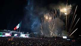 Fireworks illuminate the night sky as people gather at the Zocalo square, marking the start of celeb