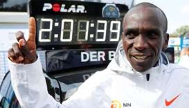 Kenya's Eliud Kipchoge celebrates winning the Berlin Marathon alongside a clock showing his World Re