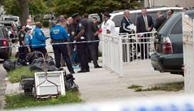 Police gather outside a daycare center in a private home after a stabbing in the Queens borough of N
