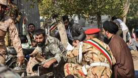 Soldiers and a Shia Muslim cleric (R) sitting close to the ground seeking cover at the scene of an a