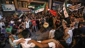 Syrians dance, chant slogans and strike drums while others and wave flags of Turkey and the oppositi