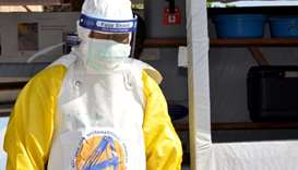 A medical worker wears a protective suit as he prepares to administer Ebola patient care at The Alli