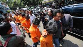 Indonesian policemen escort eights suspects of supporters of Bandung football following a violence b