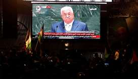 Palestinians watch a television broadcast of President Mahmoud Abbas's speech at the United Nations