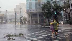 A couple crosses the street in the city centre of Naha, Okinawa prefecture as the island is the firs