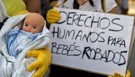 "Demonstrators hold baby dolls and placards reading ""Human rights for stolen babies"" outside a provin"