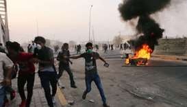 Iraqi protesters run during a protest near the building of the government office in Basra yesterday.