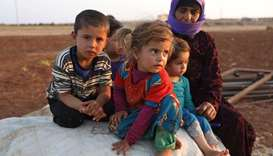 Syrian children sit next to a woman at a camp for displaced civilians - in Idlib