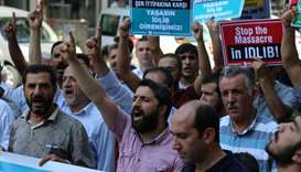 Demonstrators shout slogans during a protest against a Syrian military operation in the rebel-held I