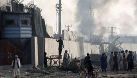 Angry Afghan protesters burn tires and shout slogans at the site of a blast