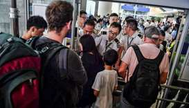 Officials assist arriving passengers near a blockade set up by protesters at Hong Kong International