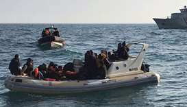 British rescuers (front) helping migrants on a semi-rigid boat
