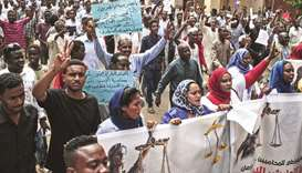 People chant slogans as they march in Khartoum yesterday with banners and signs calling for the appo