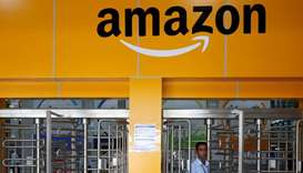 An employee of Amazon walks through a turnstile gate inside an Amazon Fulfillment Centre (BLR7) on t
