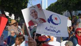 Supporters of Ennahdha's Tunisian presidential candidate Abdelfattah Mourou (portrait) attend a camp