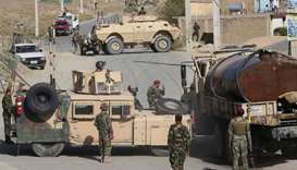 Afghan National Army (ANA) soldiers stand guard as others inspect the site