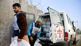 Two Red Cross workers prepare to distribute goods to detainees at a provincial prison in Afghanistan