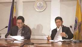 Justice Secretary Menardo Guevarra (left) and Interior Secretary Eduardo Ano sign the revised implem