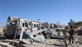 Afghan security forces investigate the site where a car bomb detonated near an intelligence services