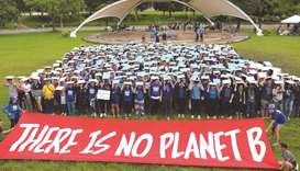 Activists comprised of students and professionals gather in front of a banner as they take part in a