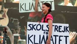 Swedish climate activist Greta Thunberg carries a sign onto the stage at the Global Climate Strike i