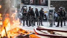 Police in riot gear stand watch past a burning barricade during clashes with pro-democracy demonstra